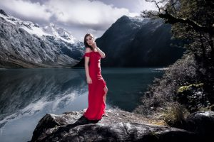 Graceful Lake - the girl in the red dress surronded by mountains - Milford Sound, New Zealand 2018