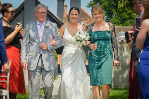 The Aisle - The bride and parents walking down the aisle for her wedding in the Sanctum on the Green, Maidenhead, England 2017